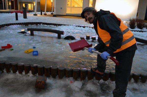 Skufler vann: Vegard prøver å få bukt med vannet på uteområdet til barnehagen.
